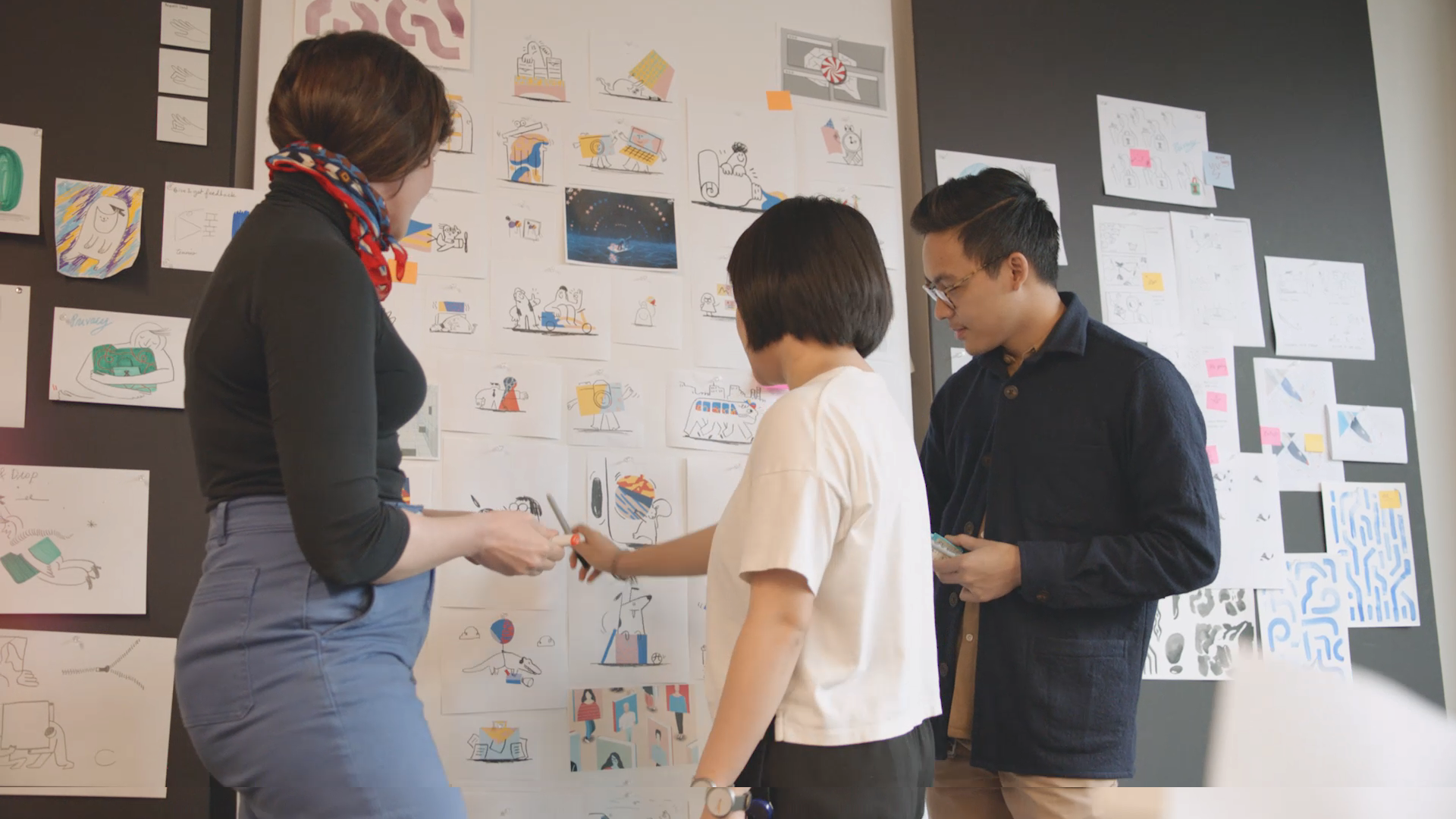 three members of the Dropbox team look at a wall with illustrations posted to it