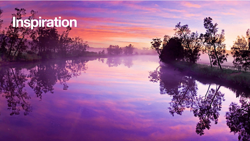 Photo of a river flanked by trees reflecting the sunset which has created deep shades of purple, pink, and orange