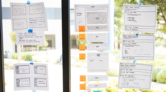 paper prototypes are taped to a window at Intuit
