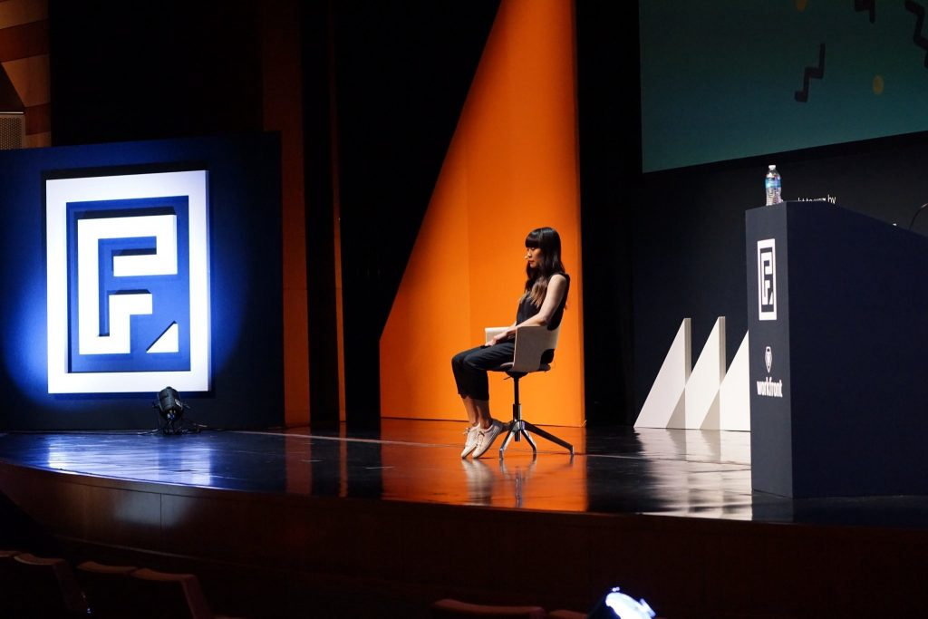 woman sits on a stage in front of lights and logos for a conference