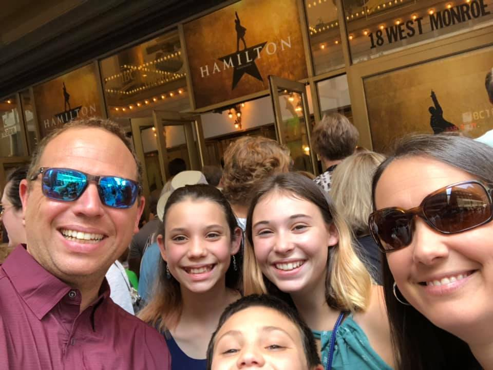 Family photo outside of Hamilton the Musical theater