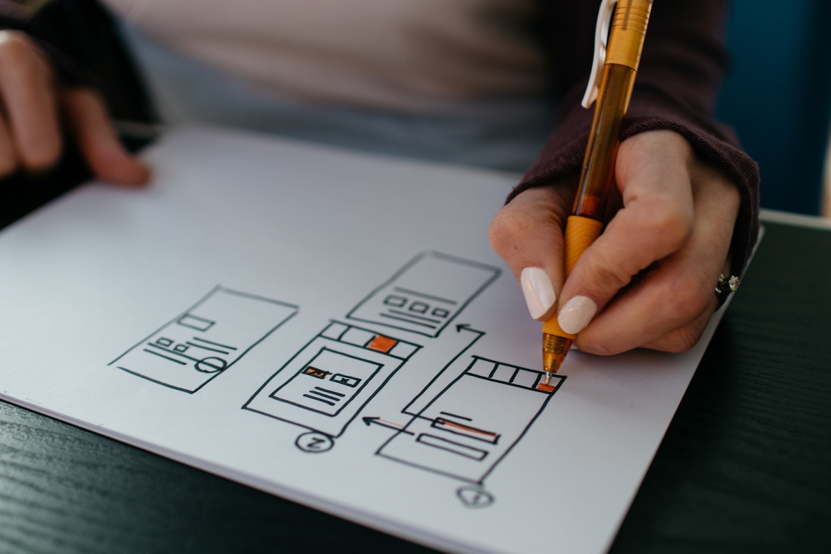 Person sketching a wireframe design on paper