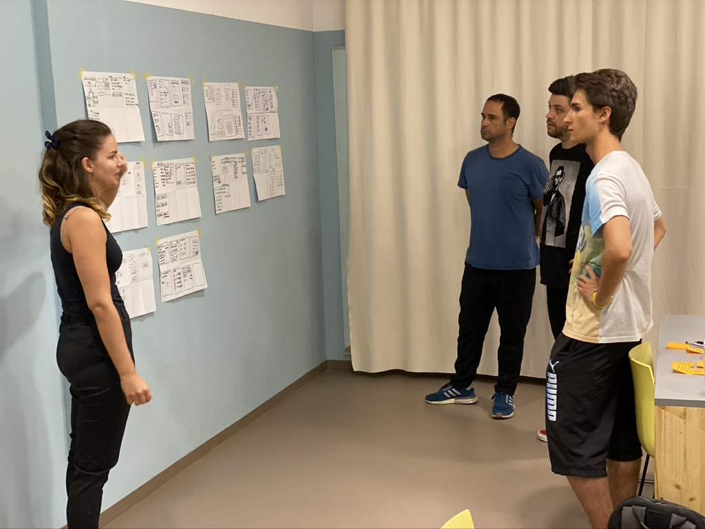 Four people standing in front of a wall posted with wireframe sketches