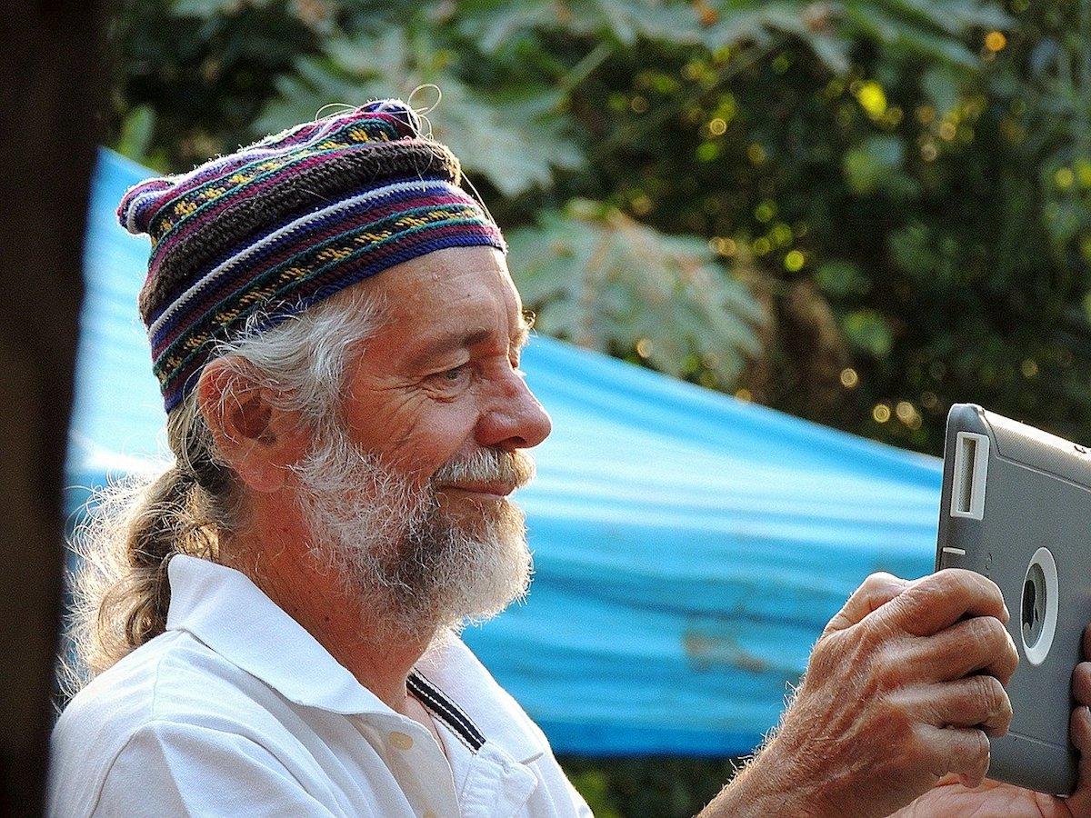 Older man using an iPad to take a photo